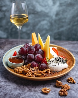Cheese plate with walnuts, grapes cheddar, goat cheese, mozzarella, blue cheese and strawberries served with white wine