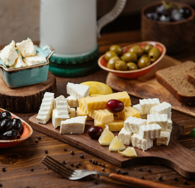 Cheese plate with white and gouda cheese, grape and lemon
