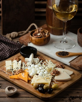 Cheese plate on wooden board with white wine