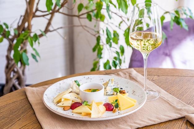 チーズの盛り合わせ。さまざまなチーズが入ったお皿。おやつ。チーズとワインのグラス。