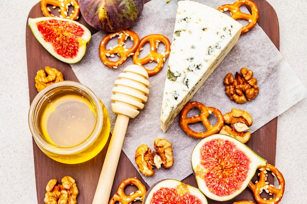 Cheese platter (board) with blue cheese, honey, walnuts, figs, pretzels