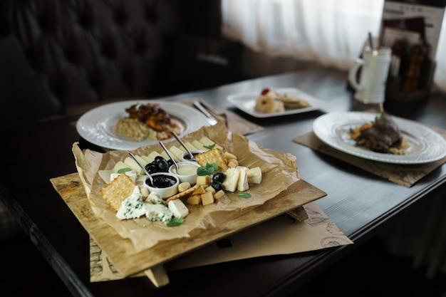 Сырное ассорти на белой тарелке стоит на деревянном винтажном столе в роскошном ресторане других блюд и кожаном диване. вкусная и полезная еда
