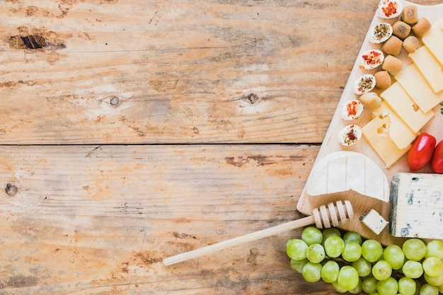 Cheese platter served with red tomatoes and grapes on wooden table