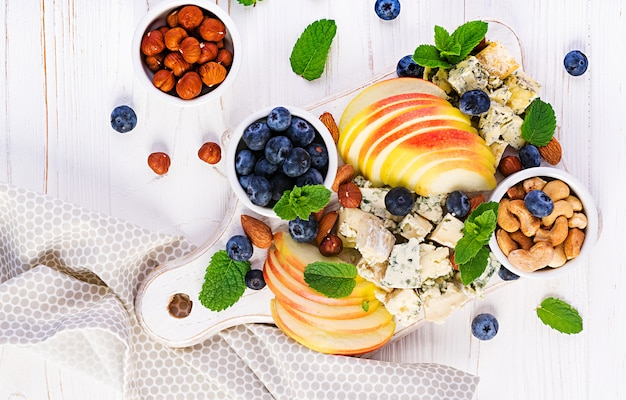 Cheese platter with assorted cheeses, blueberry, apples, nuts on white table. italian cheese  platter and fruit. top view, overhead