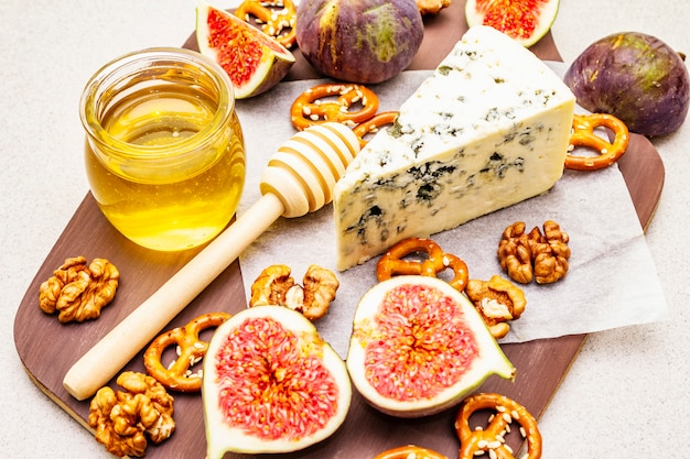 Cheese platter with blue cheese, honey, walnuts, figs and pretzels