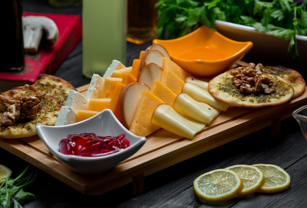 Cheese platter with cheese variations, crackers, nuts and strawberry jam