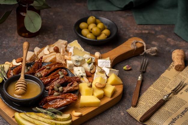 Сырное ассорти с различными сырами, вялеными помидорами, орехами, медом и финиками на деревенской деревянной доске.
