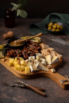 Сырное ассорти с разными сырами, вялеными помидорами, орехами, медом и финиками.