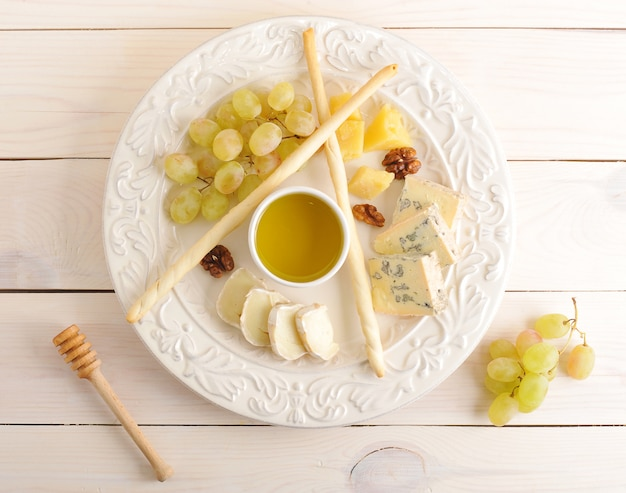 Cheese platter with grapes, honey and walnuts