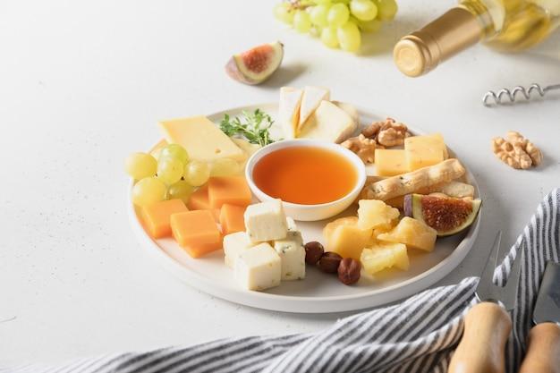 白い背景の上のブドウナッツイチジクとチーズの盛り合わせ上面図コピースペース