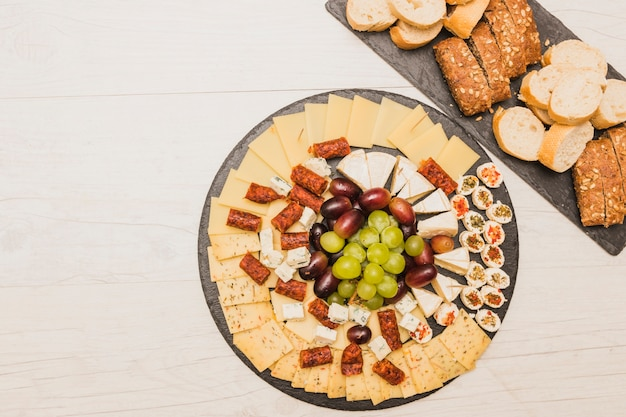 Cheese platter with grapes; smoked sausages and bread