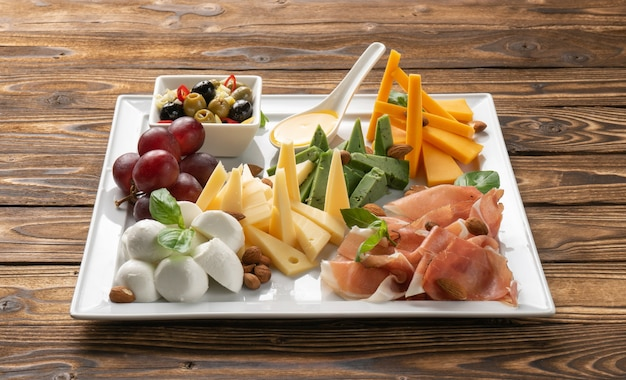 Cheese platter with parma ham, olives, olives, grapes and honey in a white ceramic plate