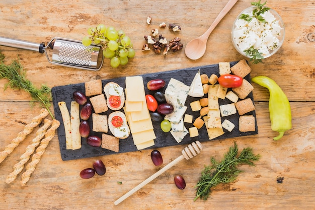 Cheese platter with parsley, grapes; honey dipper; breadsticks and green chili pepper on wooden surface