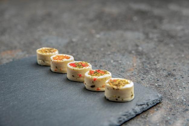 향신료와 치즈 플래터입니다. 다양한 향신료를 넣은 마짜렐라 치즈. 검은 돌 쟁반에 다양한 맛의 치즈 스낵. 음식과 간식을 주제로 한 배경 또는 배너입니다.
