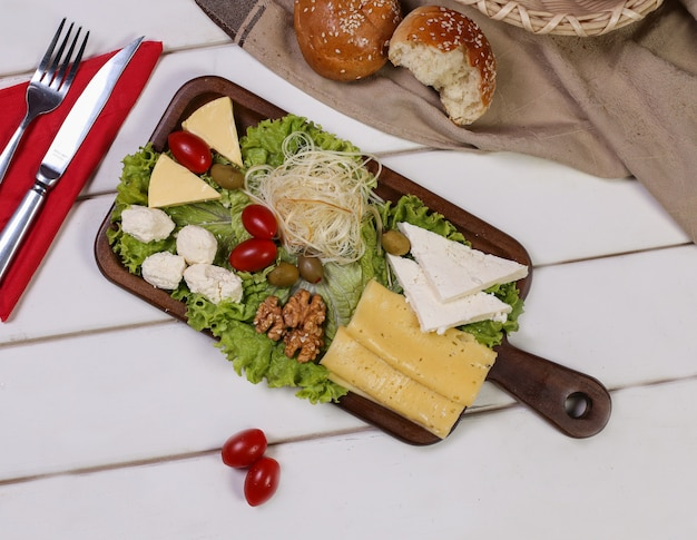 Cheese platter with tomatoes, nuts and olives with cutlery and bread buns around.