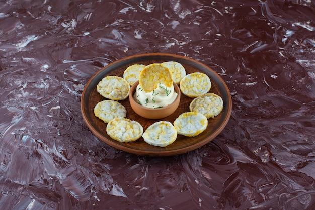 대리석 표면에 나무 접시에 치즈 감자 칩과 요구르트