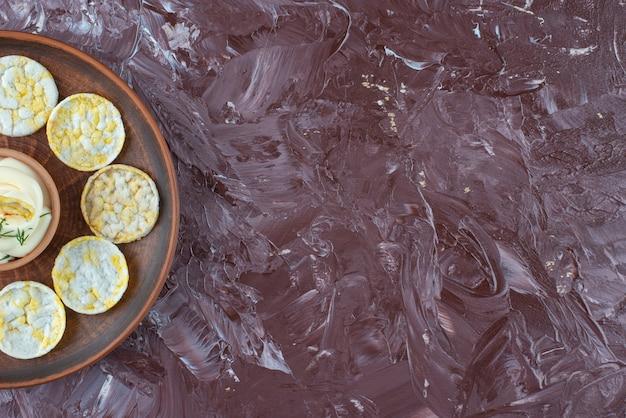 大理石のテーブルの上に、木の板にチーズポテトチップスとヨーグルト。