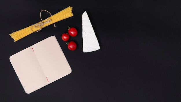 Cheese; red tomatoes; and raw spaghetti pasta with open blank diary on kitchen counter