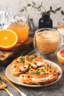Cheese and salmon toasts, breakfast concept with coffee and freshly squeezed orange juice, healthy food.