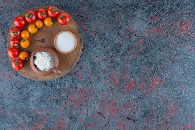 Сыр, соль и помидоры на доске, на мраморном фоне.