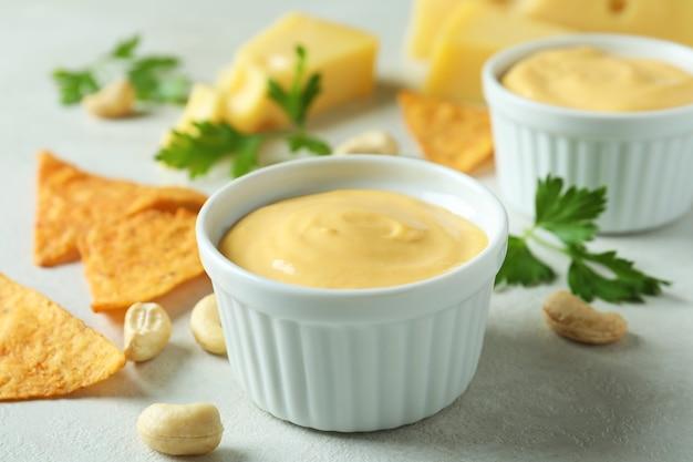 白い織り目加工のテーブルの上のチーズソースと軽食
