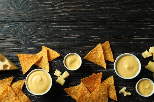 素朴な木製テーブルのチーズソース、チーズ、チップス