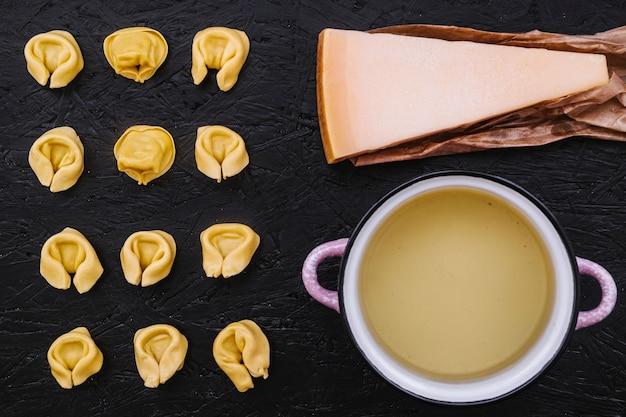 Cheese and saucepan near stuffed pasta