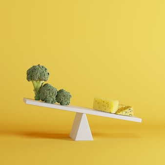 Cheese seesaw tipping with broccoli vegetables on opposite end on yellow background.