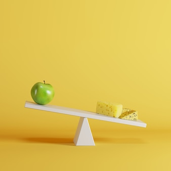Cheese seesaw tipping with green apple on opposite end on yellow background.