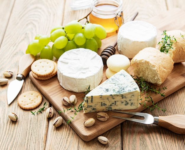 Cheese selection, honey and grape on old wooden background