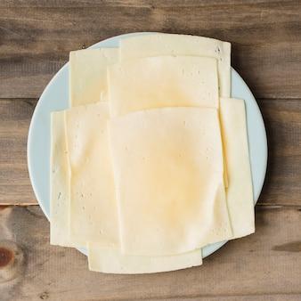 木の板を背景に白い皿にチーズスライス
