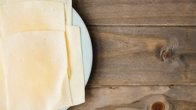 Cheese slices on white plate against wooden plank backdrop