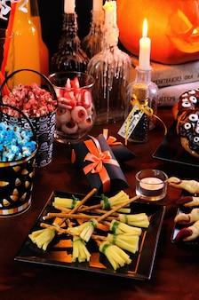 魔女のほうきの形をしたチーズスナックハロウィーンのビュッフェテーブルで提供するのに最適なアイデア