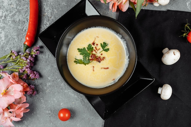 Cheese soup in a black plate on gray table.