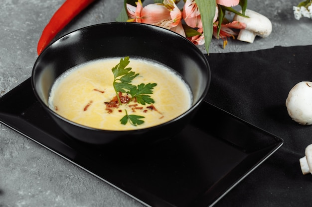 Cheese soup in a black plate on gray.