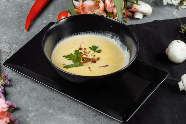 Сырный суп в черной тарелке на сером столе.