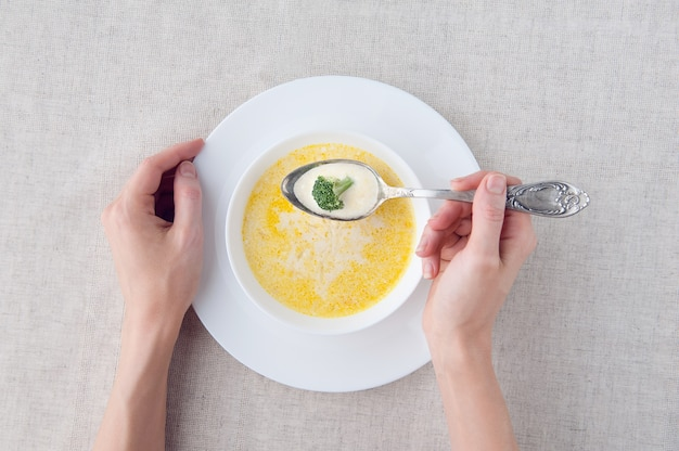 Cheese soup with broccoli in a white plate on a white linen tablecloth