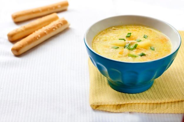 鶏肉、ジャガイモ、ターメリックとグリッシーニを背景にしたチーズスープ