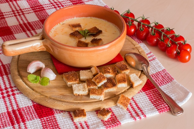 Cheese soup with crackers, cherry tomatoes and garlic