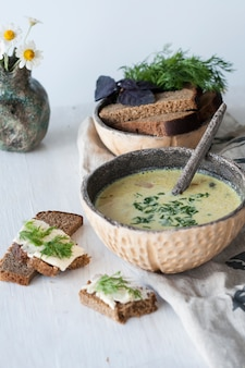 Cheese soup with mushrooms and vegetables, brown bread with butter, dill and basil on white wood