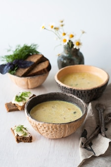 Cheese soup with mushrooms and vegetables, brown bread with butter, dill and basil