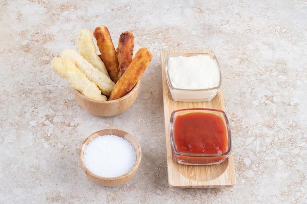 Сырные палочки и сосиски на гриле в деревянной чашке.
