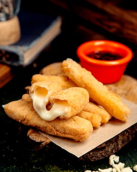 Cheese sticks in batter on a wooden hemp