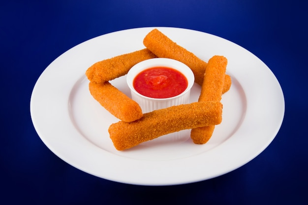 Сырные палочки в панировке с красным соусом. плоский вид сверху на белой тарелке на синем фоне.