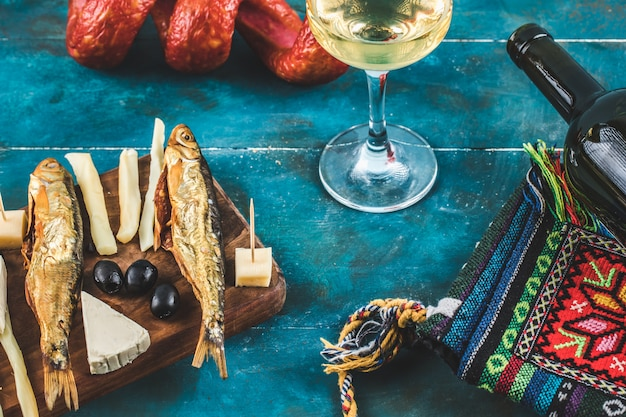 Cheese sticks with smoked fish on blue background with a glass of wine