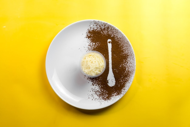 Cheese tiramisu is served on a large plate with a spoon-shaped sprinkling of coffee.