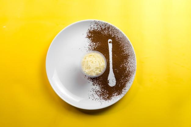 Сырный тирамису подается на большой тарелке с ложечкой, посыпанной кофе.
