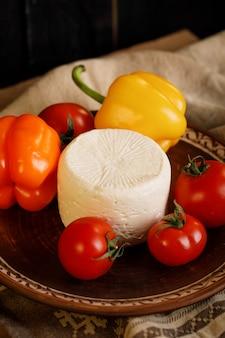 Сыр, помидоры и перец в гончарной тарелке