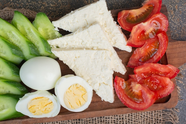 Cheese, tomatoes, boiled eggs and cucumbers on wooden board.