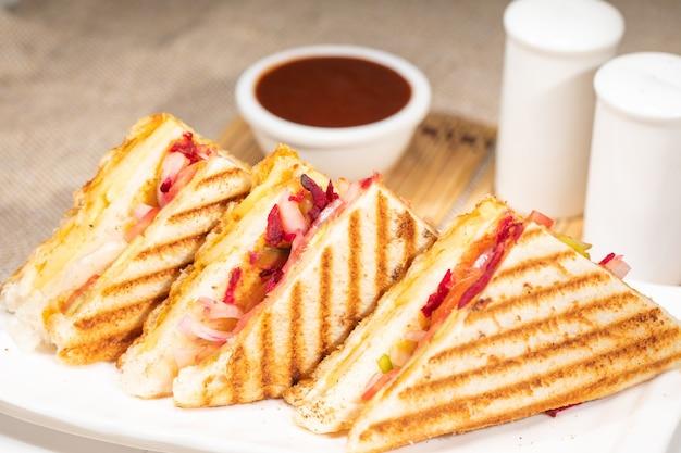 チーズ野菜のグリルサンドイッチトーストグリル朝食アイテムの上面図、プレートの白い背景。緑のチャツネサンドイッチとおいしいベジタリアンチーズ野菜